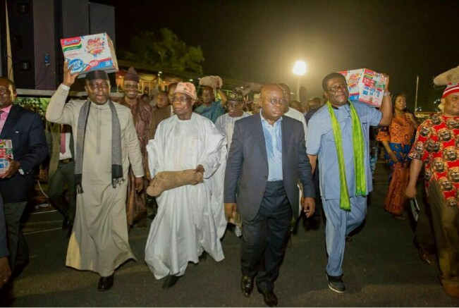 PHOTO SPEAK: Check Out Former President Olusegun Obasanjo And Richard Okorocha Carrying Yam And Indomie Cartons On The Mainroad
